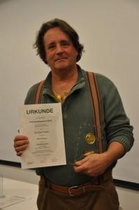 """Pierre Schmidt mit Urkunde und Preis zum Film """"Adlerflüsterer"""""""